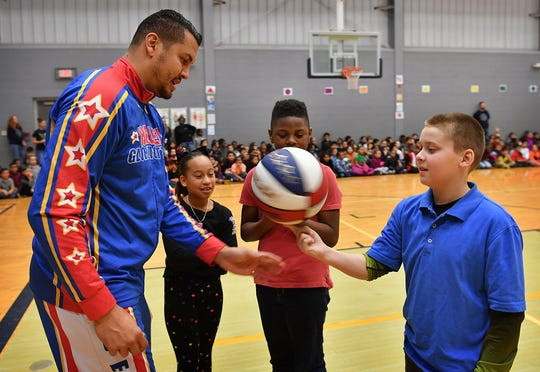 """Orlando """"El Gato"""" Melendez, a Harlem Globetrotter, teaches Chandler Ballard how to spin a basketball as his classmates, Destiny Bright and Aaron Wise look on."""