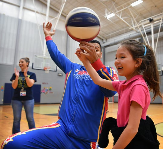 "Scotland Park second grader Caliston Barron grins as Harlem Globetrotter Orlando ""El Gato"" Melendez helps her spin a basketball on her finger during a demonstration Friday morning."