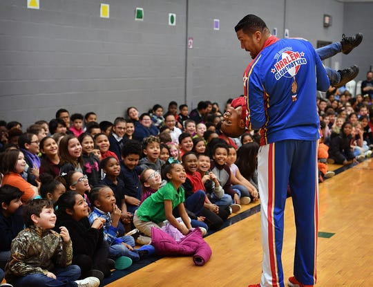 "Harlem Globetrotter Orlando ""El Gato"" Melendez uses Demetrion Combs to help demonstrate how everyone should take care of their friends during an anti-bullying presentation Friday at Scotland Park Elementary."