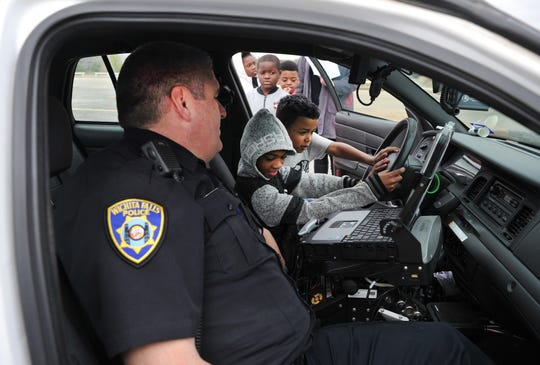 Wichita Falls police officer, Tim Johnson watched as  Booker T. Washington Elementary students took turns honking the horn and sounding the siren in his patrol car during the school's 3rd annual career day Friday morning.