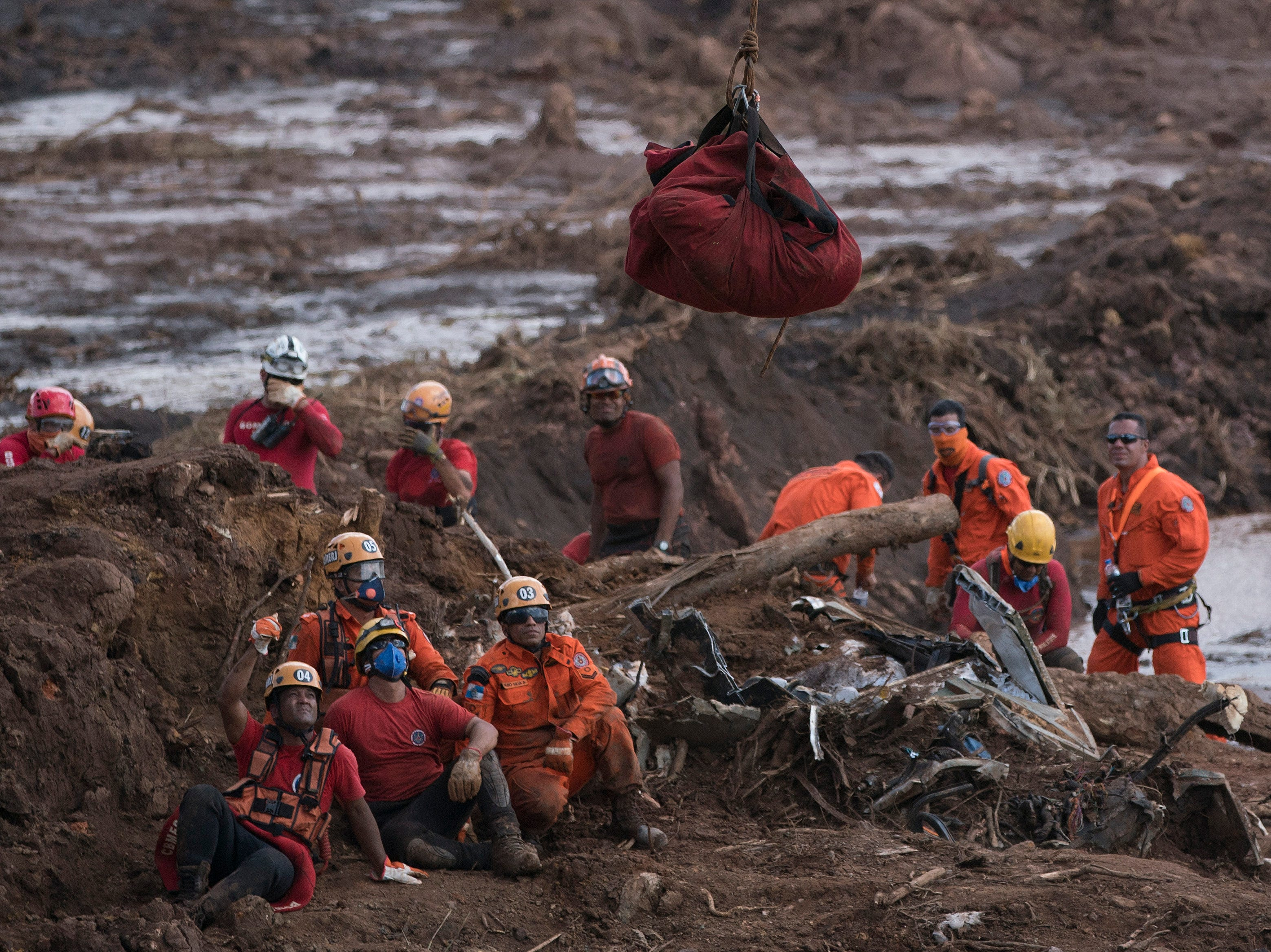 Firefighters watch the body of a person they pulled from the mud, as it is lifted up and taken away by a helicopter days after a dam collapse in Brumadinho, Brazil, Monday, Jan. 28, 2019. Firefighters on Monday carefully moved over treacherous mud, sometimes walking, sometimes crawling, in search of survivors or bodies four days after a dam collapse that buried mine buildings and surrounding neighborhoods with iron ore waste.