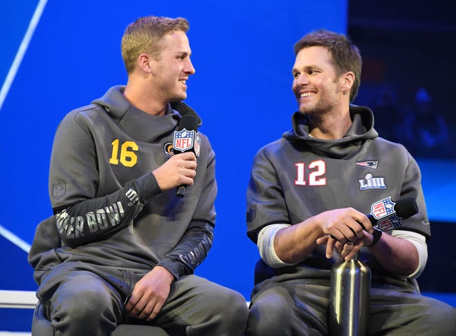 Jan 28, 2019; Atlanta, GA, USA; Los Angeles Rams quarterback Jared Goff (16) and New England Patriots quarterback Tom Brady (12) talk on stage during Opening Night for Super Bowl LIII at State Farm Arena. Mandatory Credit: Kirby Lee-USA TODAY Sports
