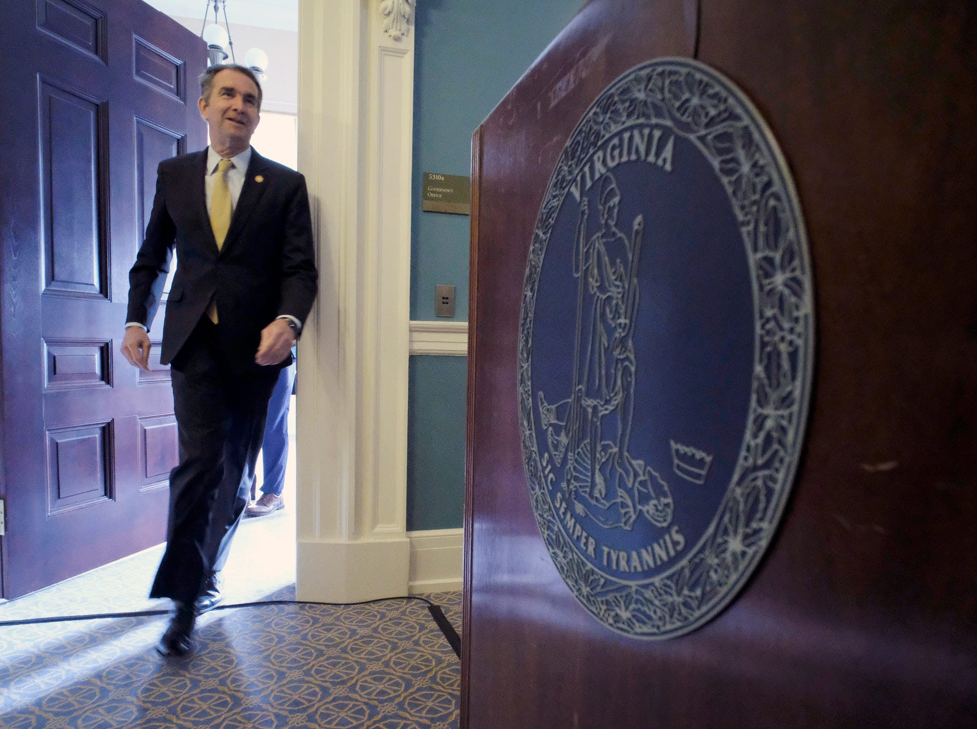 Virginia Governor Ralph Northam enters his conference room and heads for the podium, right, where he previewed several of his legislative proposals relating to elections during a media event at the State Capitol in Richmond, Va., Monday, Jan. 7, 2019.