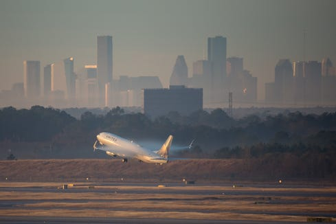 The skyline of downtown Houston rises behind a United Airlines Boeing 737 as it departs George Bush Intercontinental Airport on Jan. 27, 2019.