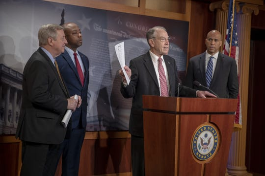 Sens. Dick Durbin, D-Ill.,  Tim Scott, R-S.C.,  and Cory Booker, D-N.J.,  listen to Senate Judiciary Committee Chairman Chuck Grassley, R-Iowa,  talk about passage of the First Step Act at a press conference  Dec. 19, 2018 in Washington, D.C.