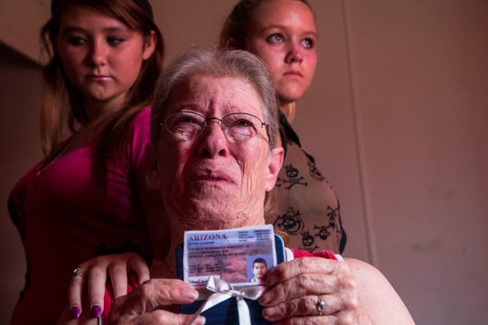 Portrait of Martha McKee and her grandchildren, Rayann Martinez, 13, on left, and Martha Lee Martinez, 12. McKee holds her son Thomas Martinez's drivers license photo on July 18, 2014, at her home in Apache Junction, Arizona. He was having mini-seizures when police delivered two five-second, 50,000-volt electrical jolts to him at a Noodles & Company restaurant. He became unresponsive on the scene with no pulse, slipped into a coma and died a few days later at a nearby hospital.