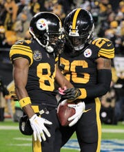 Pittsburgh Steelers wide receiver Antonio Brown (84) celebrates his touchdown catch with running back Le'Veon Bell (26) against the Tennessee Titans during the third quarter at Heinz Field.