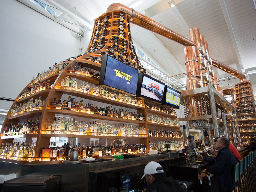 The impressive bar at Q, a barbecue restaurant, towers over patrons at George Bush Intercontinental Airport in Houston on Jan. 27, 2019.