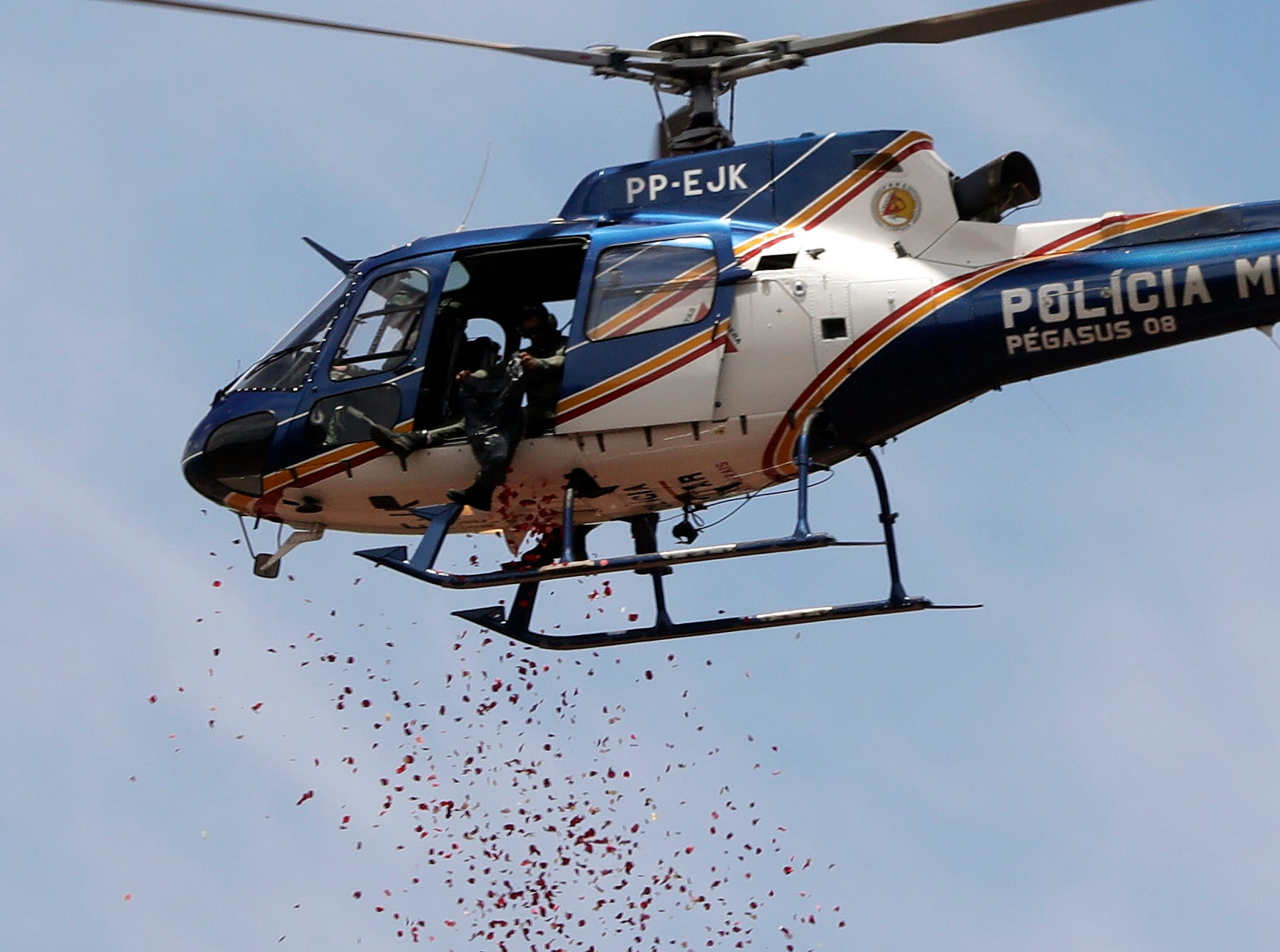 A helicopter releases flower petals on top of an iron ore mining complex paying homage to the 110 victims killed and 238 who are still missing after a mining dam collapsed there a week ago, in Brumadinho, Brazil, Friday, Feb. 1, 2019.