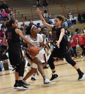 Alexandria Senior High's Honisti Thompson (31) and Kayln Washington (20) defend a Pineville player during a game last season.