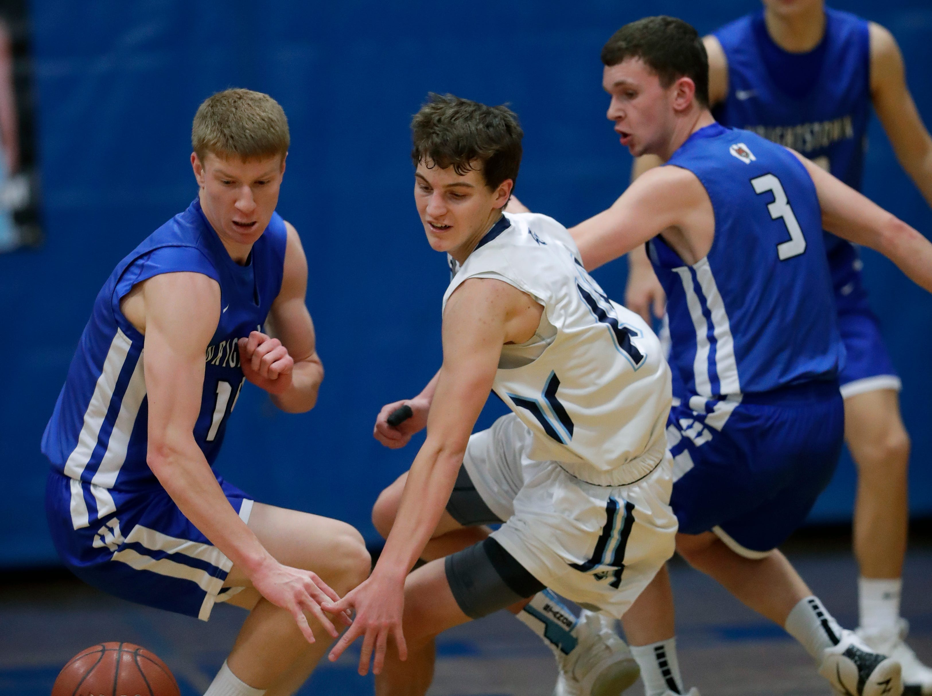 Little Chute High School's Logan Plate, center, battels for a loose ball against Wrightstown High School's Mayson Hazaert, left, and Will Braeger (3) during their boys basketball game Friday, February 1, 2019, in Little Chute, Wis. 