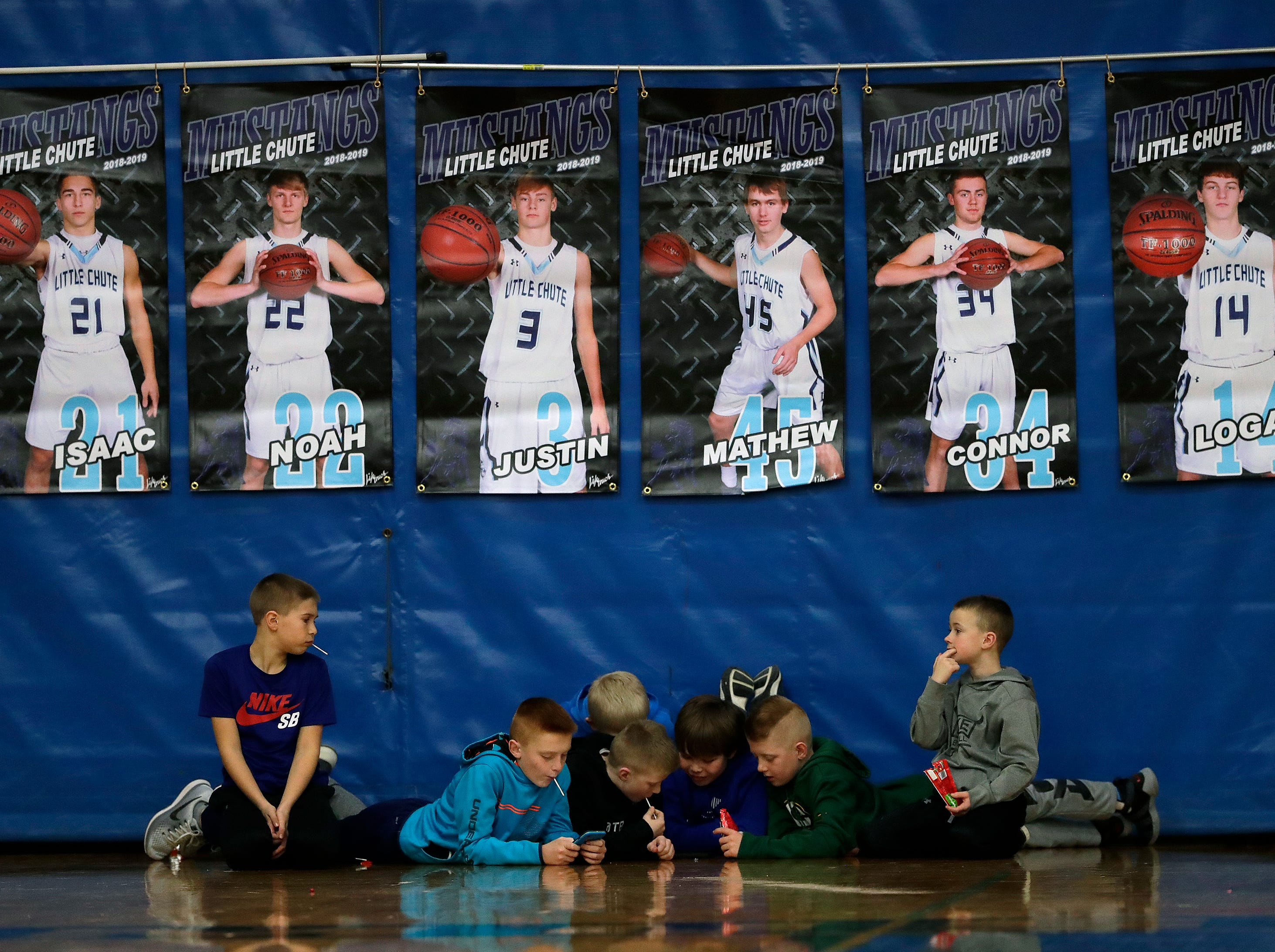Young Little Chute High School fans have better things to do as their team plays against Wrightstown High School during their boys basketball game Friday, February 1, 2019, in Little Chute, Wis. 