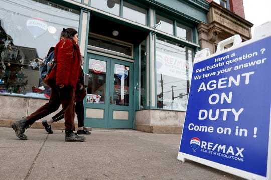 People walk by a real estate office in Pittsburgh's Lawrenceville neighborhood. Even if it's a stretch now, buying your first home by age 35 can mean more wealth in retirement.