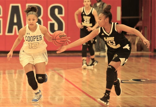 Cooper's Aziah Joe (13) brings the ball upcourt as Wichita Falls Rider's Taleyah Jones (23) ties to knock the ball away. Cooper beat the Lady Raiders 35-27 in the District 4-5A game Friday, Feb. 1, 2019, at Cougar Gym. The win clinched a playoff berth for the Lady Coogs.