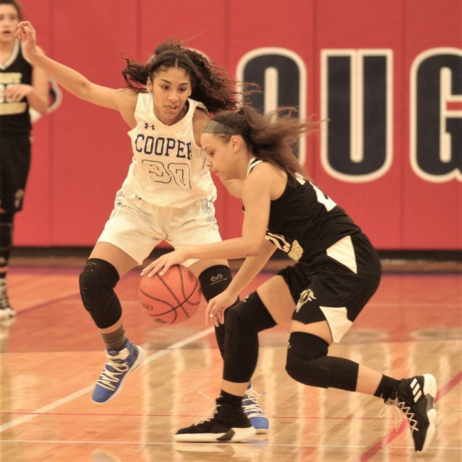 Cooper's Keiana Kemp (30) defends against Wichita Falls Rider player. Cooper beat the Lady Raiders 35-27 in the District 4-5A game Friday, Feb. 1, 2019, at Cougar Gym. The win clinched a playoff berth for the Lady Coogs.