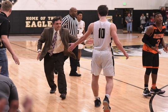 Abilene High coach Justin Reese gives Landon Talley (10) a high-five late in Friday's game against Haltom City Haltom. The Eagles earned a 59-57 victory at home with a buzzer-beater.