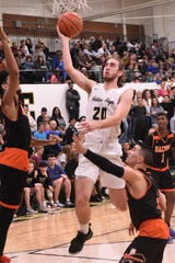 Abilene High's Brian Patton (20) goes over a Haltom City Haltom defender for a layup at Eagle Gym on Friday night. Patton scored 14 points in the first half as the Eagles won 59-57 on a buzzer-beater.