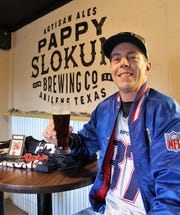 Patriots fan Josh Baker brought memorabilia to Pappy Slokum's on Saturday, including a Tom Brady rookie card that he bought in 2001 as an add-on for a Willie McGinnis card. Total cost: $3.  He is wearing a 1986 Patriots jacket, over a Ron Gronkowski No. 87 jersey.