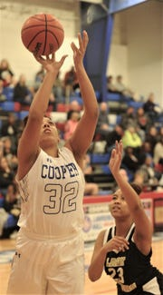 Cooper's Jennika Willis (32) shoots as Wichita Falls Rider's Taleyah Jones defends. Cooper beat the Lady Raiders 35-27 in the District 4-5A game Friday, Feb. 1, 2019, at Cougar Gym. The win clinched a playoff berth for the Lady Coogs.