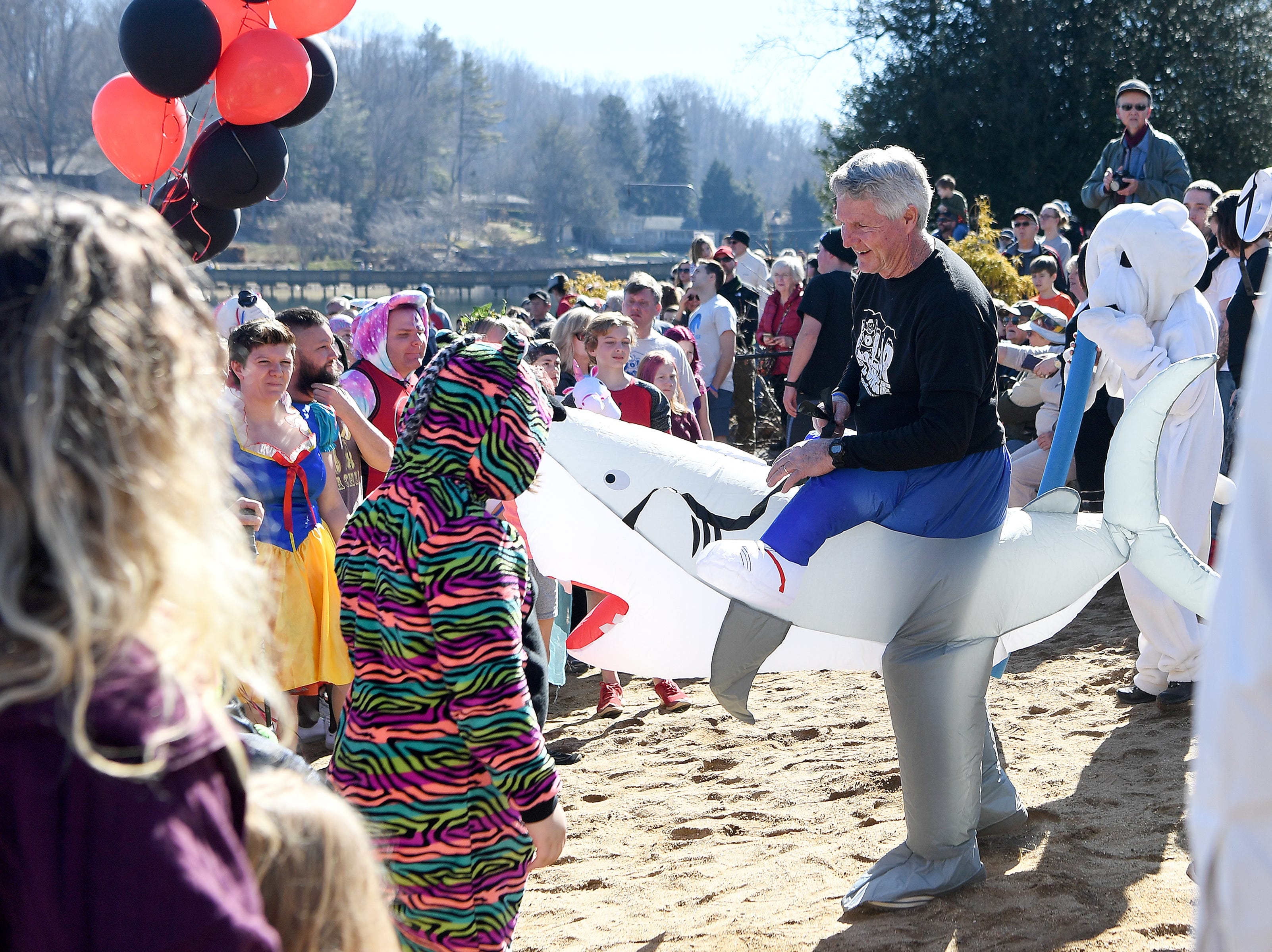 Dan Ebaugh, property manager at Lake Junaluska Conference and Retreat Center and Haywood Waterways board member, navigates his shark costume onto the beach with the other plungers during the 7th Annual Plunge at Lake Junaluska Conference and Retreat Center on Feb. 2, 2019. The event raised more than $30,000 for Kids in the Creek and environmental education.