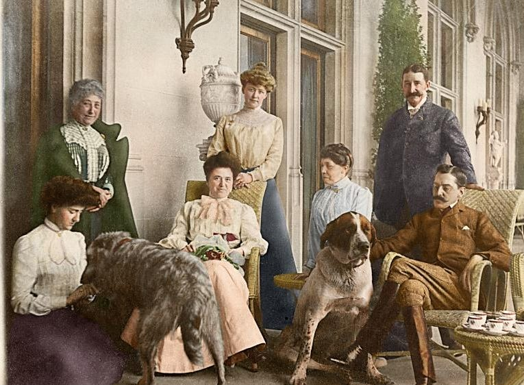 This colorized version of a photograph from the Vanderbilt archives depicts afternoon tea on the Loggia of Biltmore House with the Vanderbilts, May 1903. From left, Edith Vanderbilt, Mademoiselle Rambaud (Edith Vanderbilt's former chaperone), Lila Vanderbilt Webb (George Vanderbilt's sister), Mary Webb (Lila Webb's sister in law), Isabella Stewart Gardner, William Blodgett II, and George Vanderbilt.