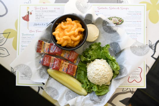 The Classic Carol at Chicken Salad Chick is made with all white meat shredded chicken, finely minced celery, mayonnaise and a secret seasoning. Shown here with macaroni and cheese.