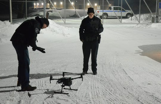 Battle Creek Corporal Andrew Olsen, left and officer Jed Reames prepare to launch the department's drone to search for a missing inmate. The inmate from the Calhoun County Jail was recaptured about 10 a.m.