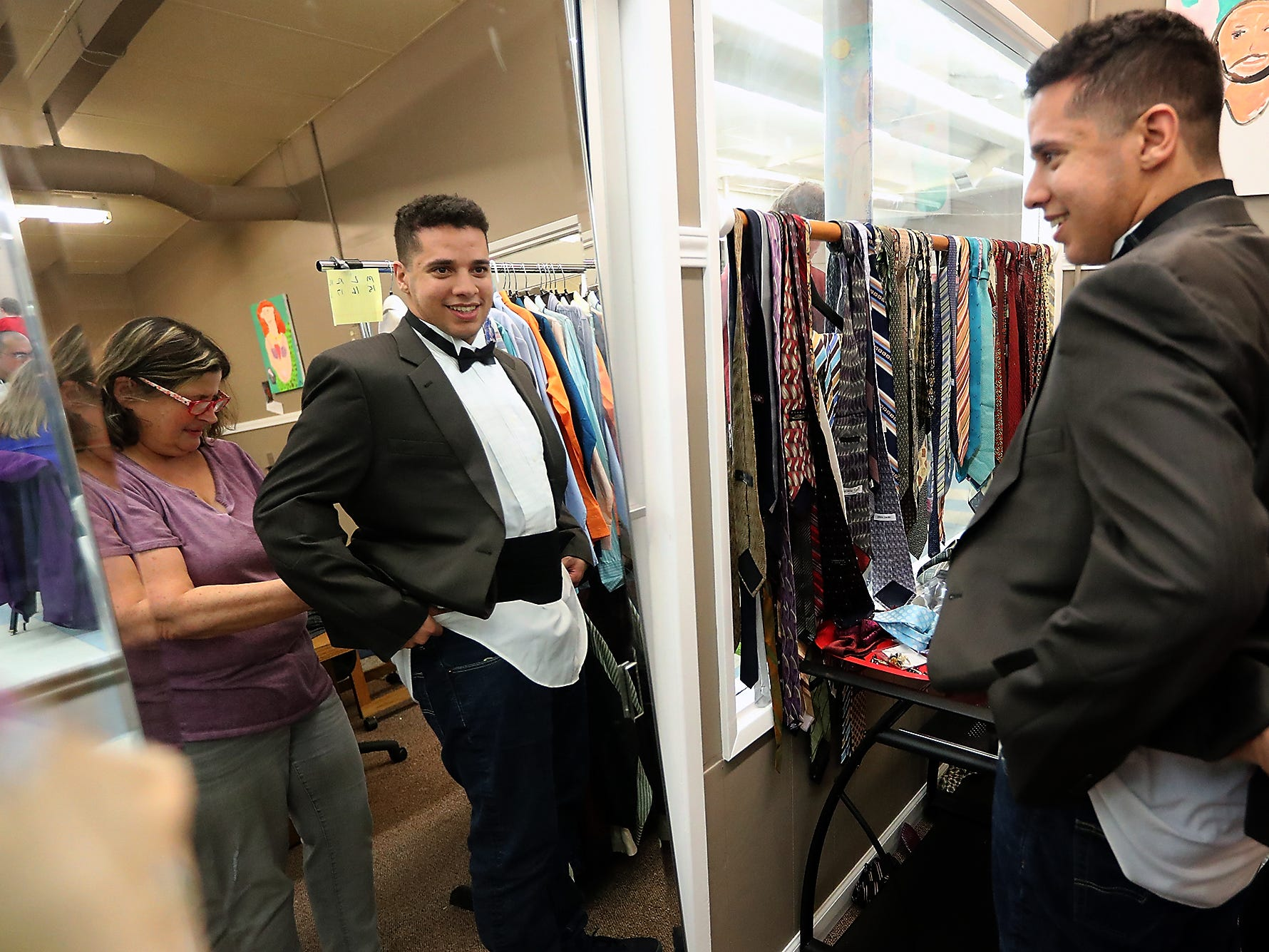 Volunteer Jeanie Johns (left) helps Robin Miller try on a cummerbund to wear to the upcoming Night To Shine Prom,  at the Arc of the Peninsulas in Bremerton on Friday. Night To Shine attendees were able to visit the dress shop at the Arc of the Peninsulas and pick out donated suits, dresses and accessories to wear to the upcoming formal event. Night to Shine takes place on Friday, Feb. 8 at the Kitsap Sun Pavilion.