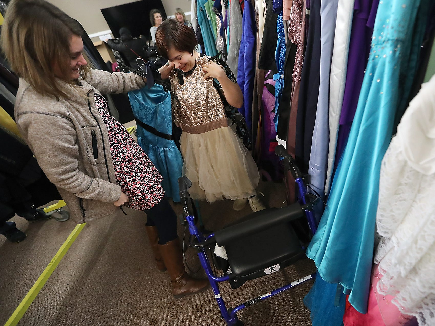 Taylor Webster (left), of Cascade Community Connection, holds a dress against Kaitlyn Winn, as the two shop for a dress for Winn to wear to her first Night To Shine prom, at the Arc of the Peninsulas in Bremerton on Friday, February 1, 2019. Night To Shine attendees were able to visit the dress shop at the Arc and pick out donated suits, dresses and accessories to wear to the upcoming formal event which will take place on February 8th at the Kitsap Sun Pavilion.
