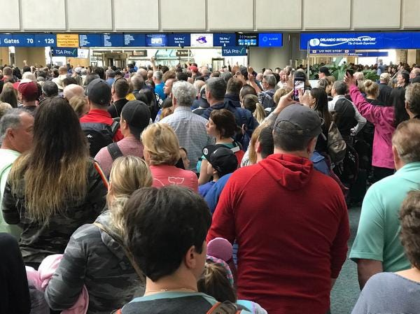 """People wait to get through security at the Orlando International Airport following a security incident on Saturday, Feb. 2, 2019. Passengers on shuttles to gates at Florida's busiest airport had to be brought back for a second screening, bringing security checkpoints to a temporary standstill. A spokeswoman for Orlando International Airport told television station WKMG on Saturday that the passengers were returned in """"an abundance of caution"""" after some passengers may have gotten through the checkpoints without being screened property.  (Jonathan Hayward/The Canadian Press via AP)"""