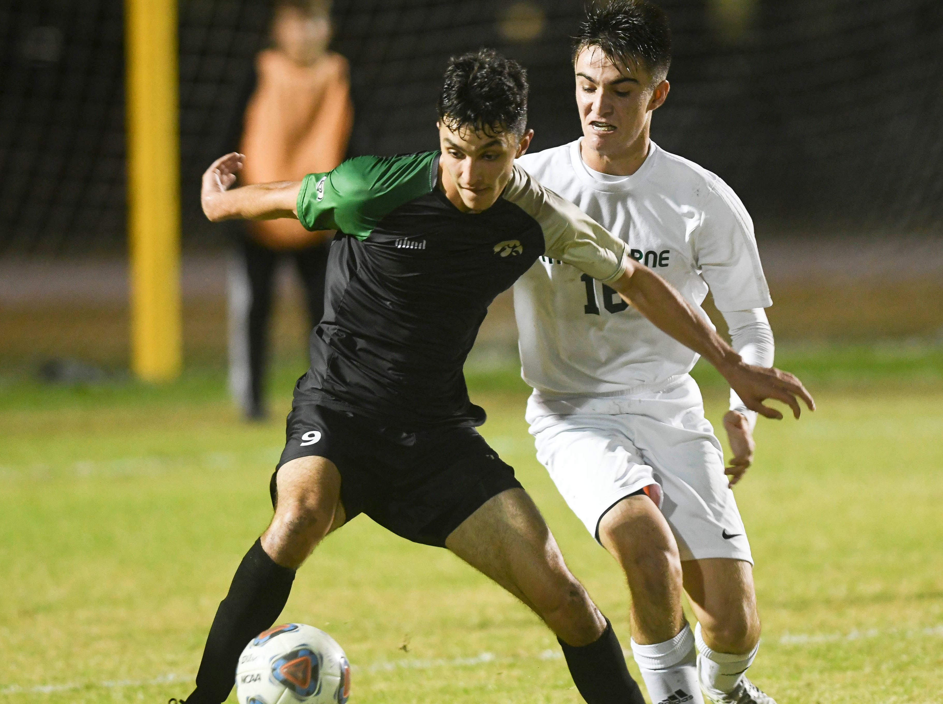 Viera's Kia Mohajeri and Calvin MacDonald of Melbourne fight for the ball during Friday's game at Viera High.
