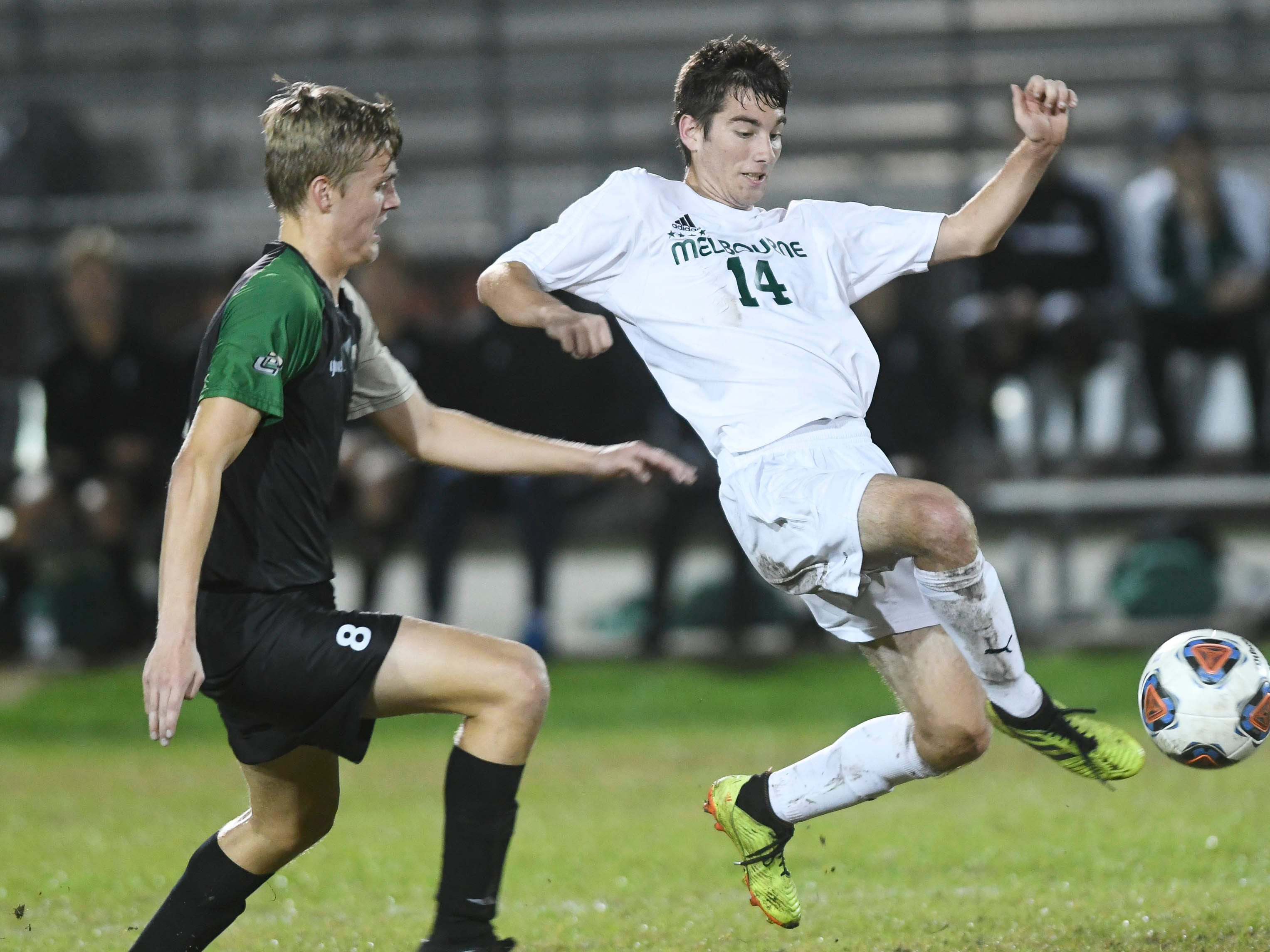 Melbourne's Dylan Barakat (14) drives the ball away from Mads Jensen of Viera during Friday's game at Viera High.