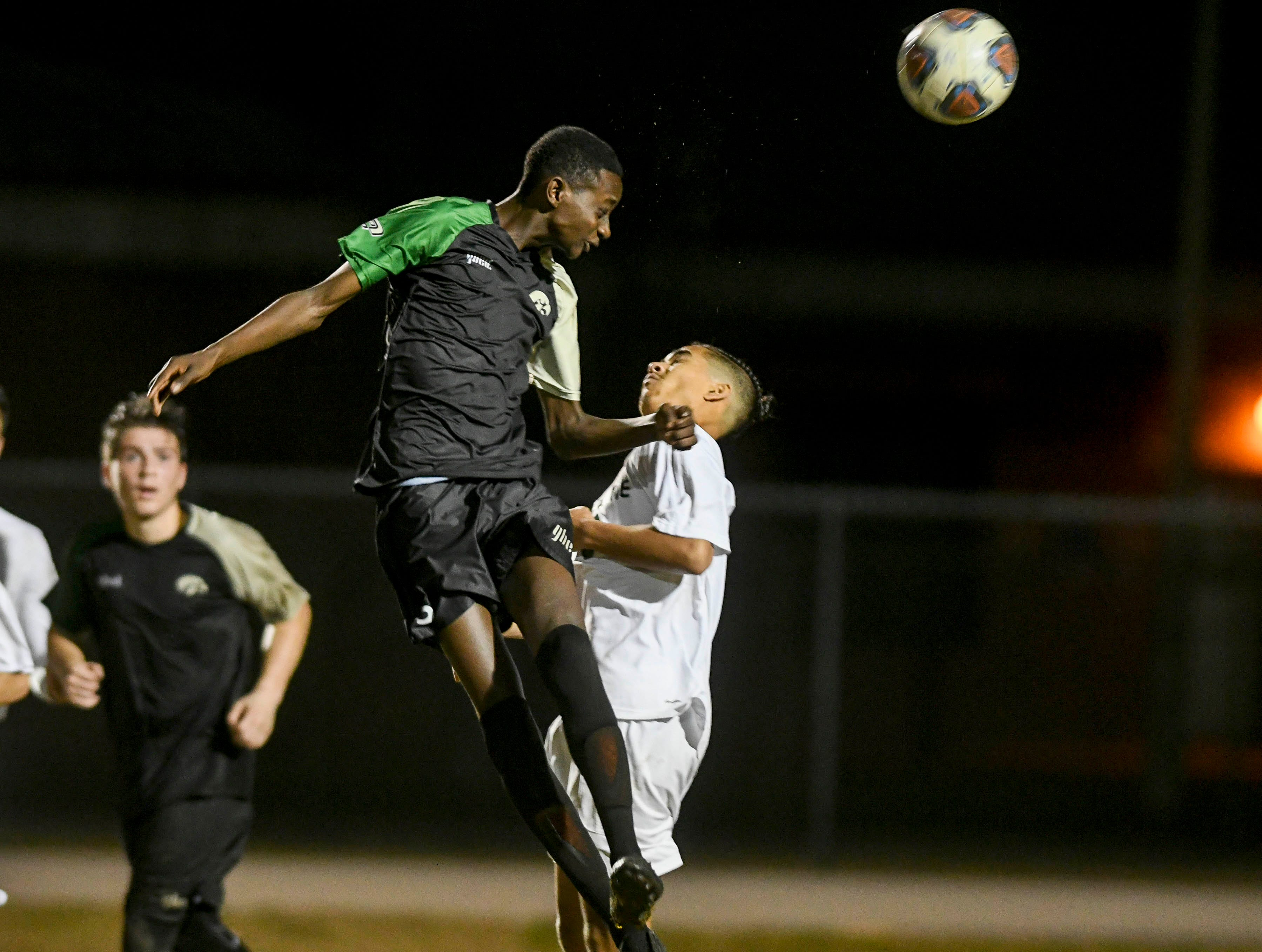 Nyles Lockridge of Viera heads the ball away from Mekhi Robinson of Melbourne during Friday's game at Viera High.