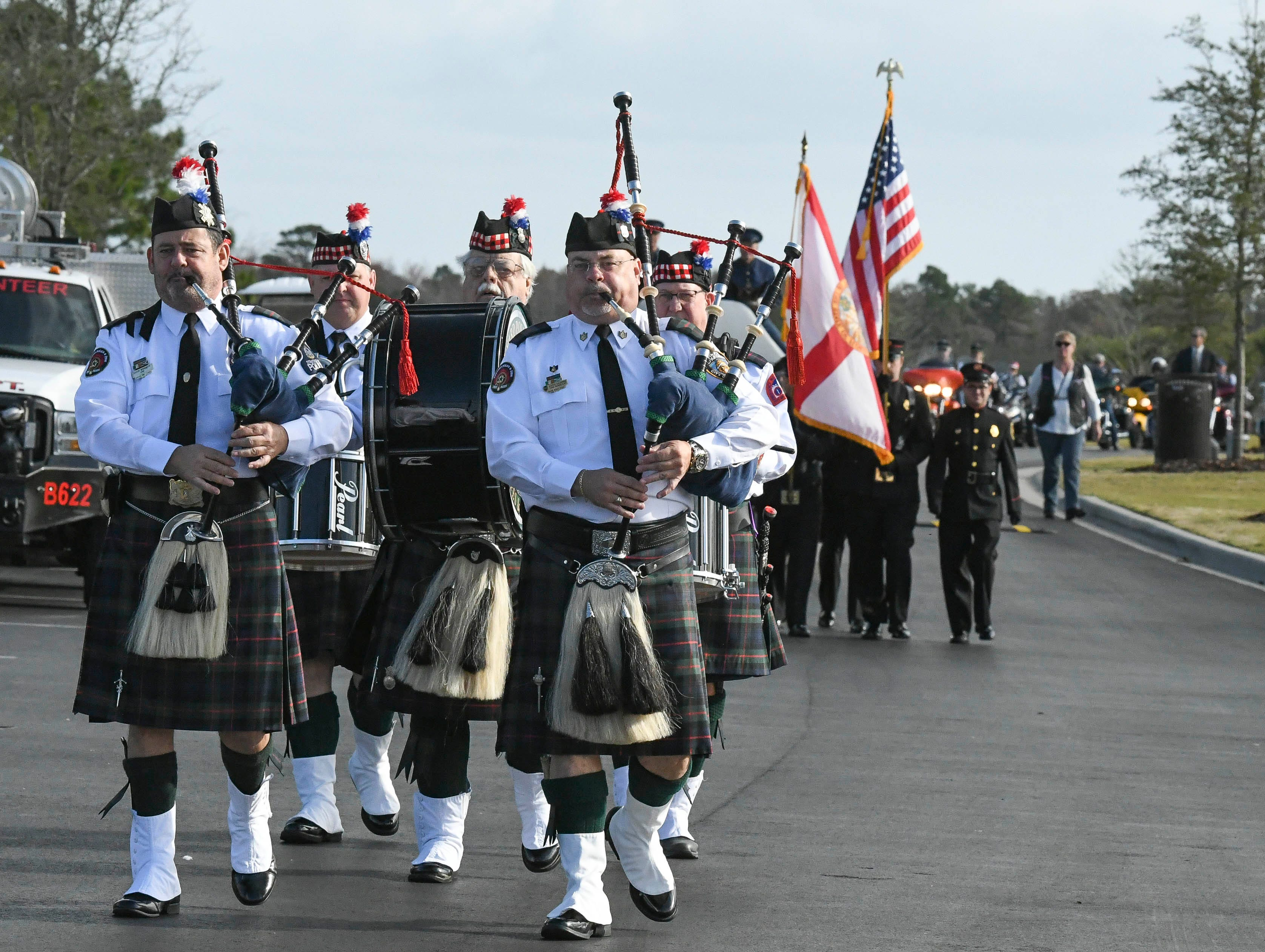 The Brevard Police and Fire Pipes and Drums Band leads the way as the ashes of 19 veterans and six spouses are laid to rest in a ceremony Saturday lat Cape Canaveral National Cemetery. The Missing in America Project heads up the effort to locate and inter the unclaimed cremains of veterans throughout the country.
