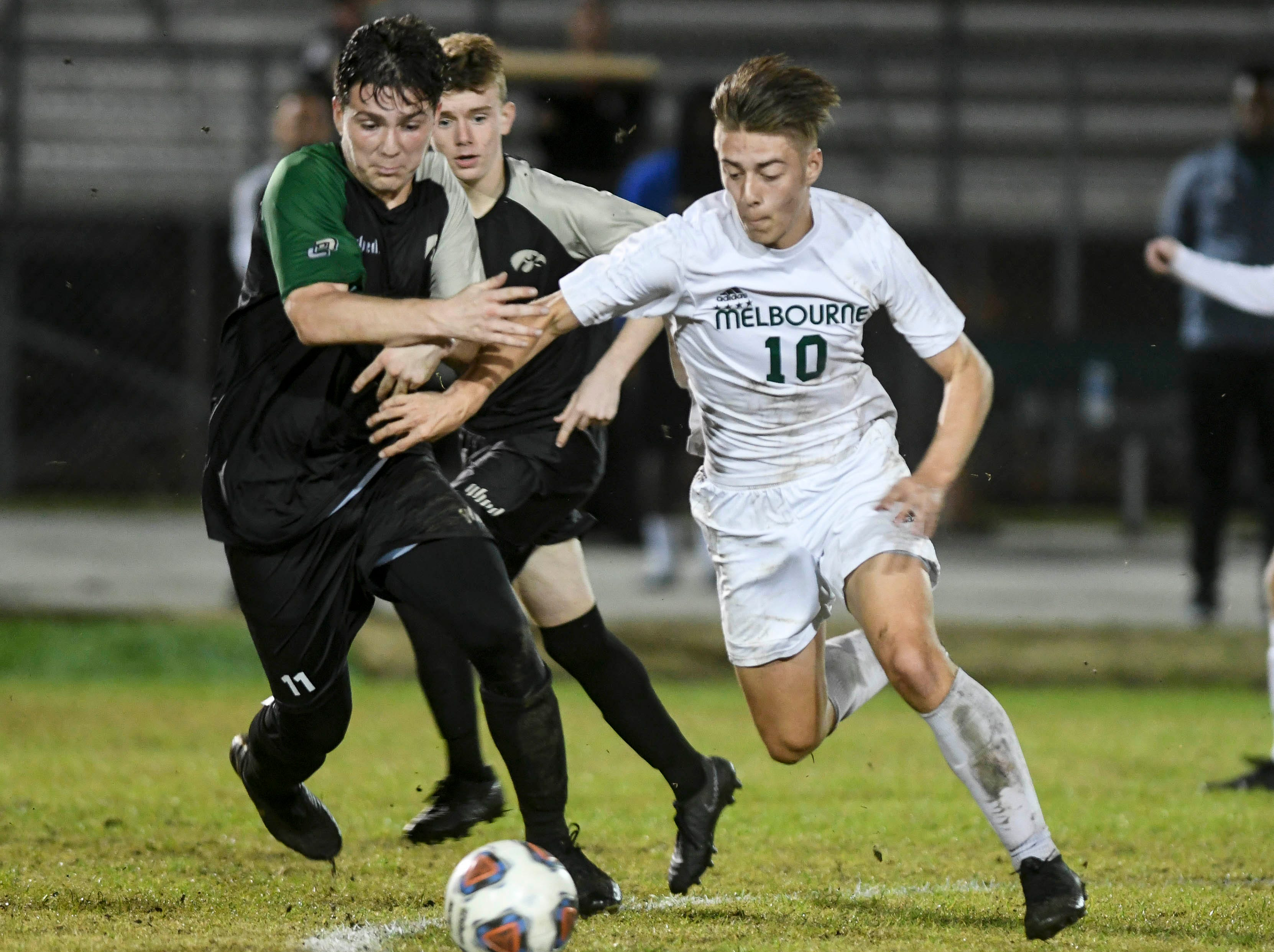 Christian Becerra of Viera and Aden O'Hara of Melbourne fight for the ball during Friday 's district championship game at Viera High.
