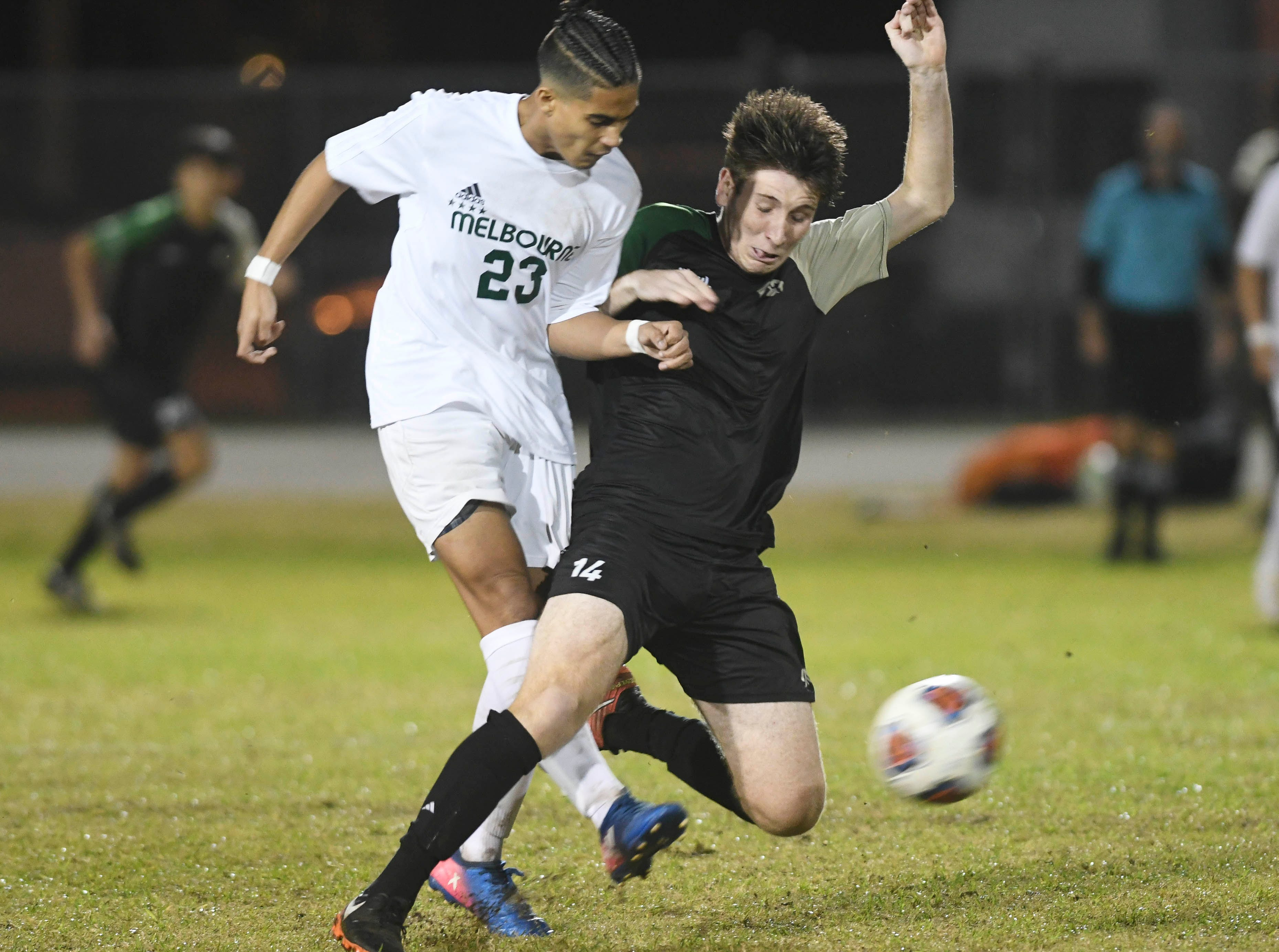 Melbourne's Mekhi Robinson (23) and Patrick Murtha of VIera battle for the ball during Friday's game.