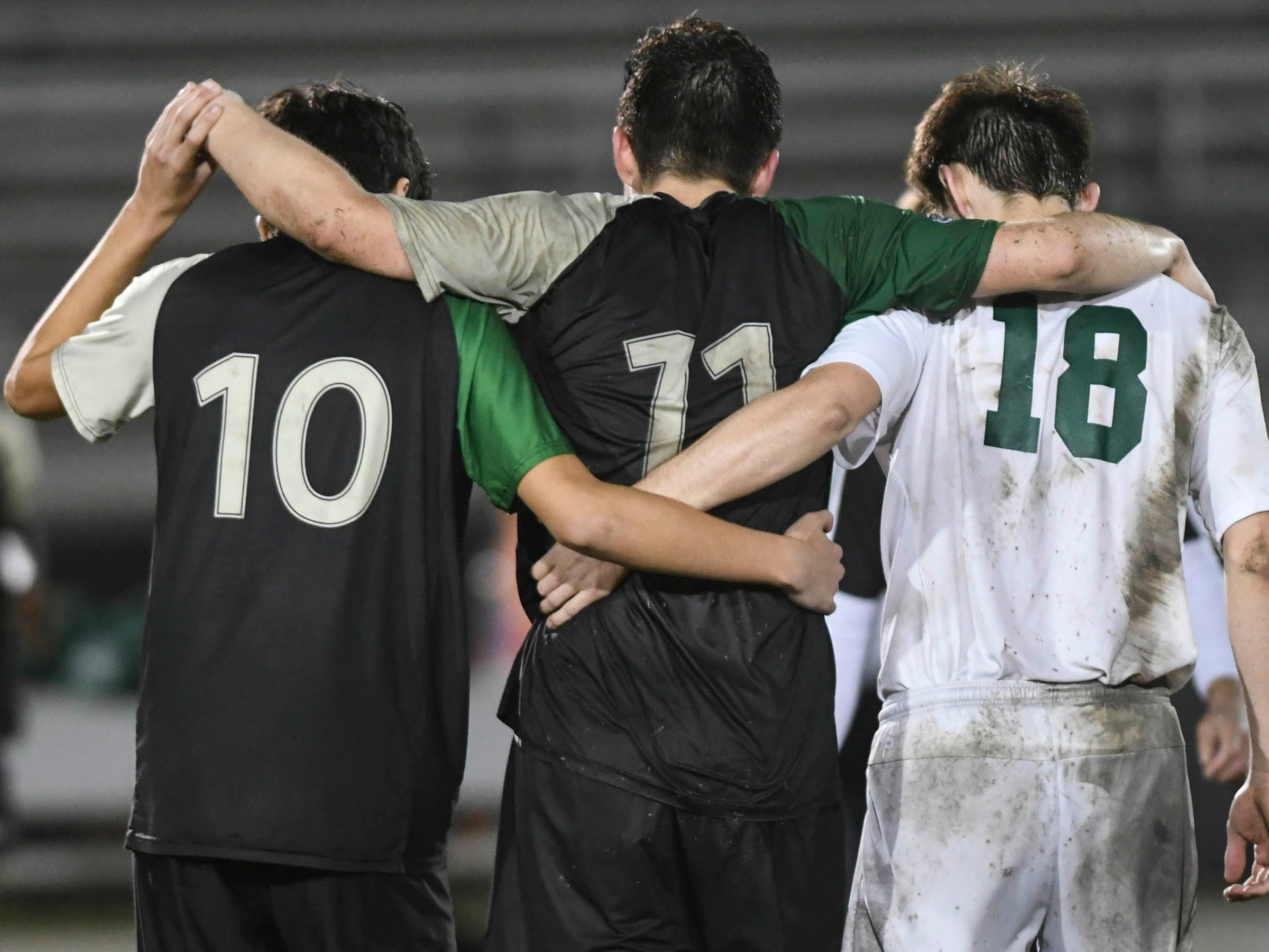 Viera's Kyle Hupfer (10) and Melbourne's Cooper Bywater (18) help Christian Becerra off the field after he was injured in Friday's district championship game at Viera High.