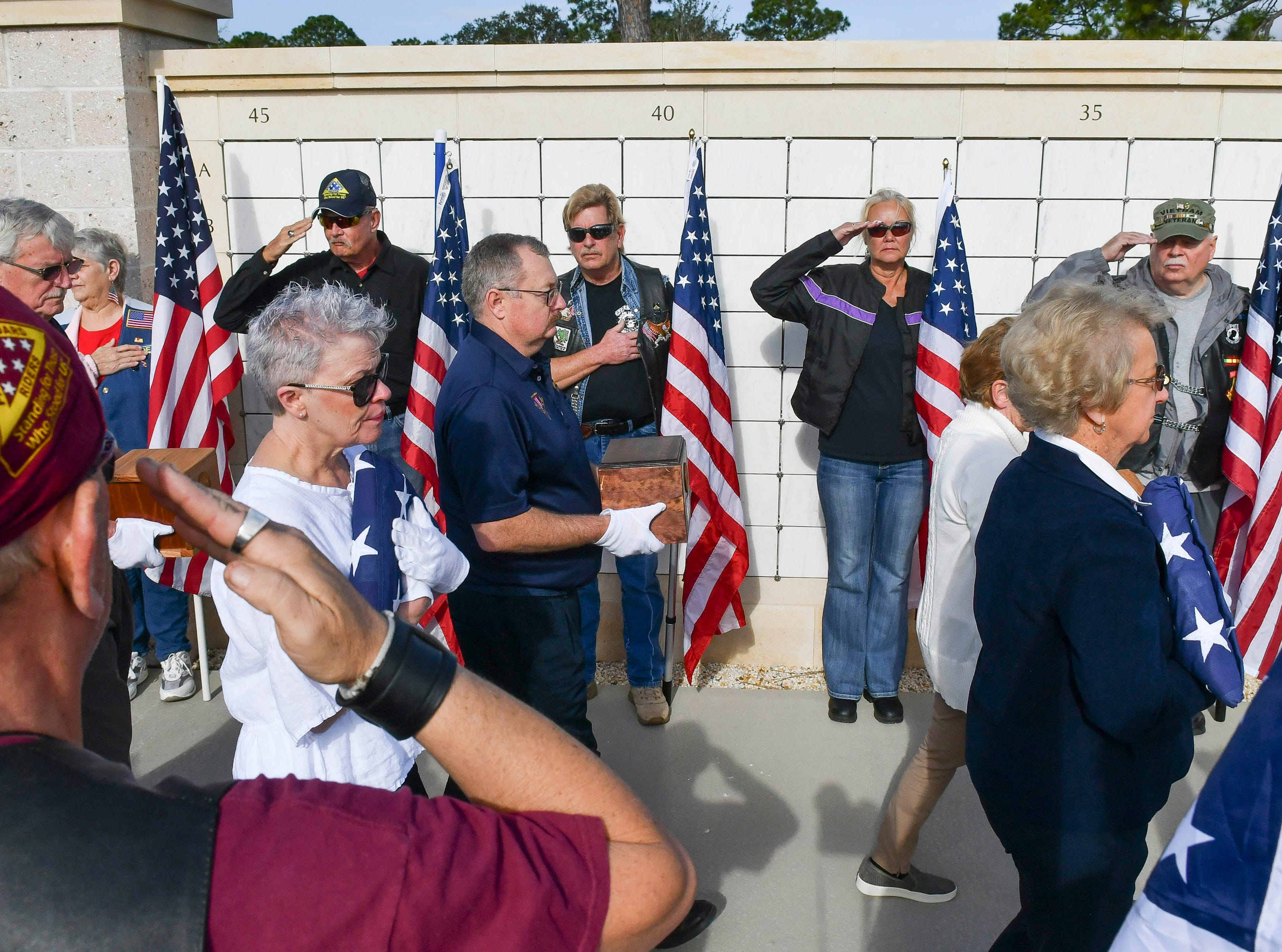 Members of the Patriot Guard riders salute as the ashes of 19 veterans and six spouses are laid to rest in a ceremony Saturday lat Cape Canaveral National Cemetery. The Missing in America Project heads up the effort to locate and inter the unclaimed cremains of veterans throughout the country.