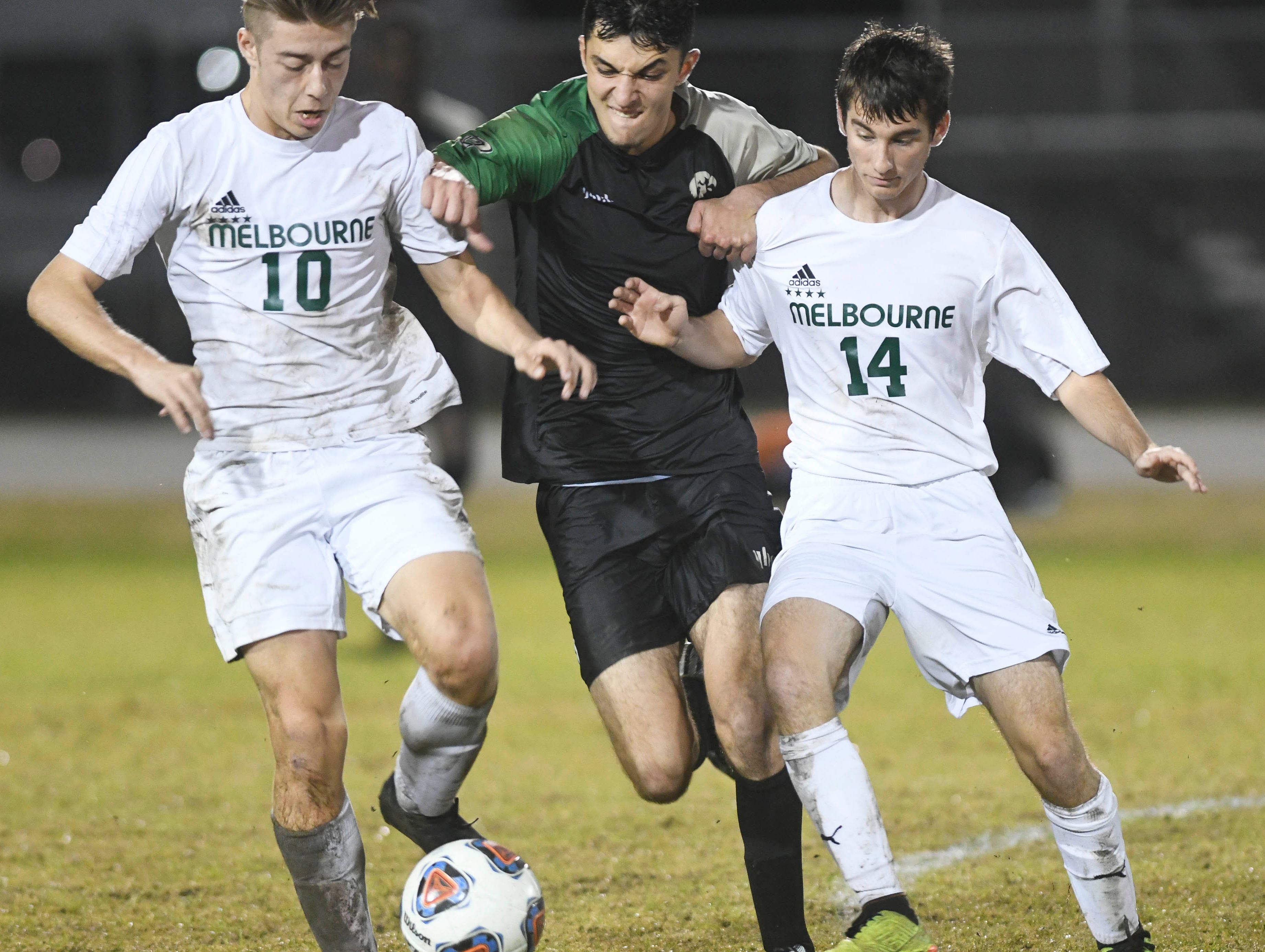Aden O'Hara of Melbourne (10), Kia Mohajeri of VIera and Dylan Barakat of Melbourne fight for the ball during Friday's game at Viera High.