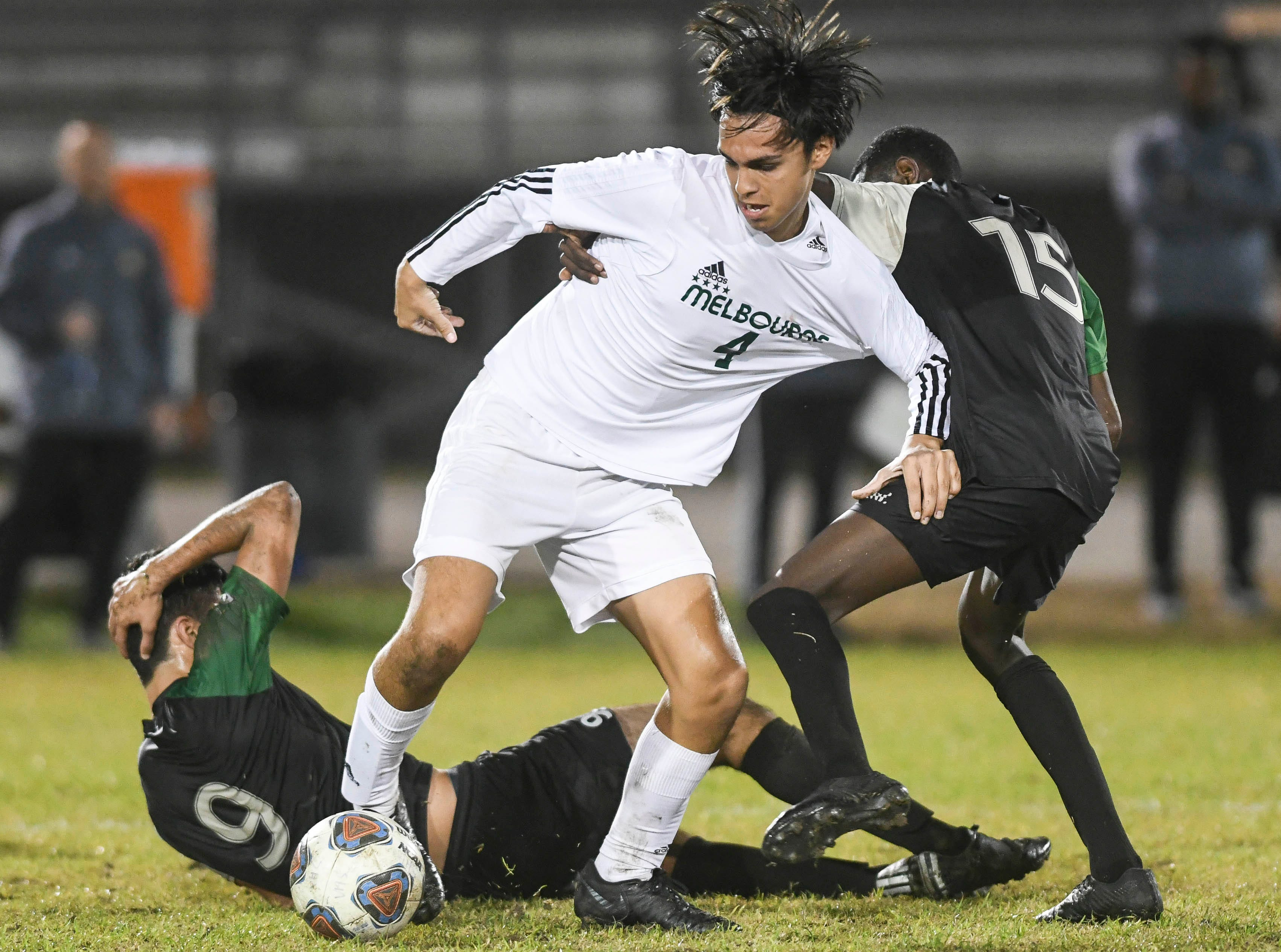 Nick Martinez of Melbourne (4), Kia Mohajeri of Viera and Nyles Lockridge of Viera (15) scramble for the ball during Friday at Viera High.'s Class 4A, District 6 championship game.