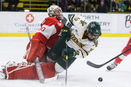 Vermont's Val Caldwell (19) battles for the puck with Boston goalie Corinne Schroeder (30) during the women's hockey game between the Boston Terriers and the Vermont Catamounts at Gutterson Field House on Friday night February 1, 2019 in Burlington, Vermont.