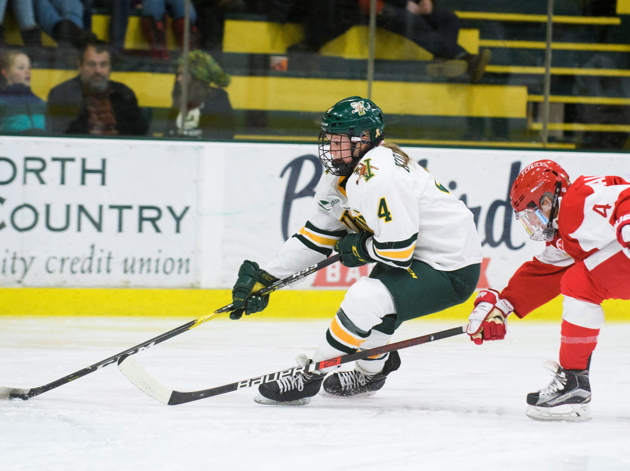 Vermont's Sammy Kolowrat (4) skates with the puck past Boston's Alexandra Calderone (4) during the women's hockey game between the Boston Terriers and the Vermont Catamounts at Gutterson Field House on Friday night February 1, 2019 in Burlington, Vermont.S)