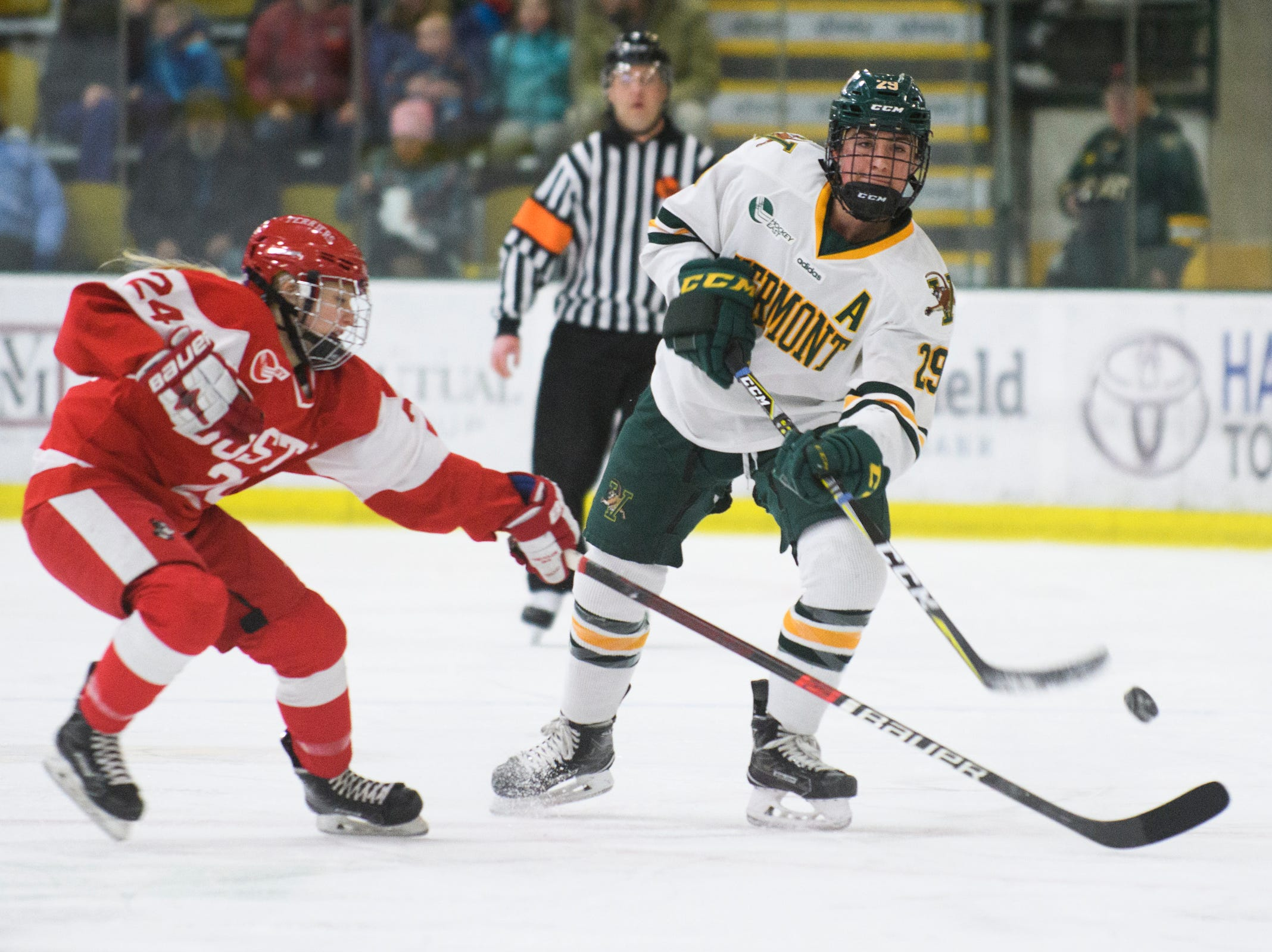 Vermont's Taylor Flaherty (29) dumps the puck into the zone past Boston's Mary Grace Kelley (24) during the women's hockey game between the Boston Terriers and the Vermont Catamounts at Gutterson Field House on Friday night February 1, 2019 in Burlington, Vermont.