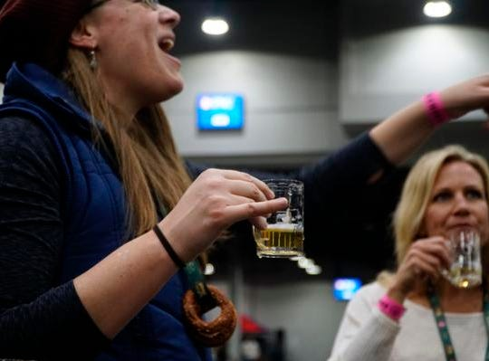 Robbie Paulsen lifts a pinky finger after sampling her first beer, the Sierra Nevada Brut IPA, at the Cincy Winter Beerfest in the Duke Energy Convention Center, Saturday, Feb. 2, 2019.