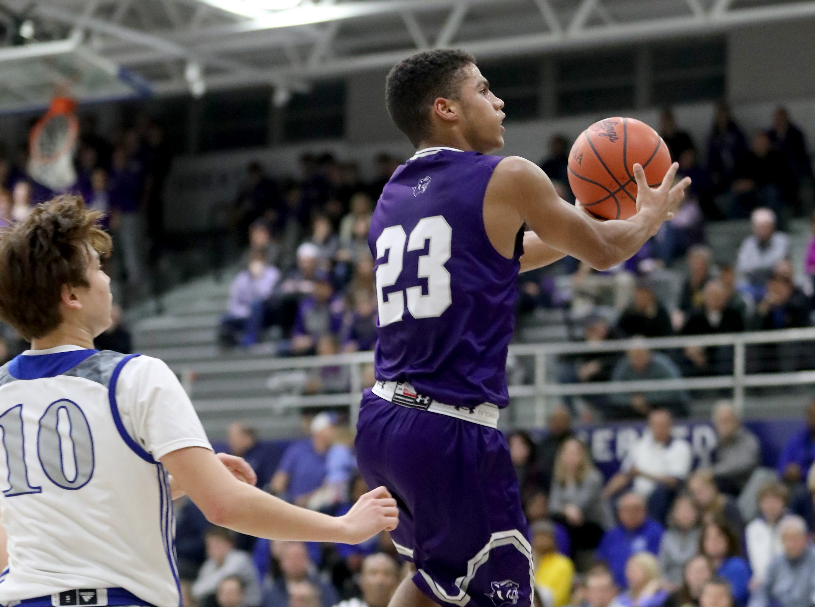 Elder guard Bryson Merz (23) drives to the basket past St. Xavier guard Nathan  Stockman during their basketball game Friday, Feb. 1, 2019.