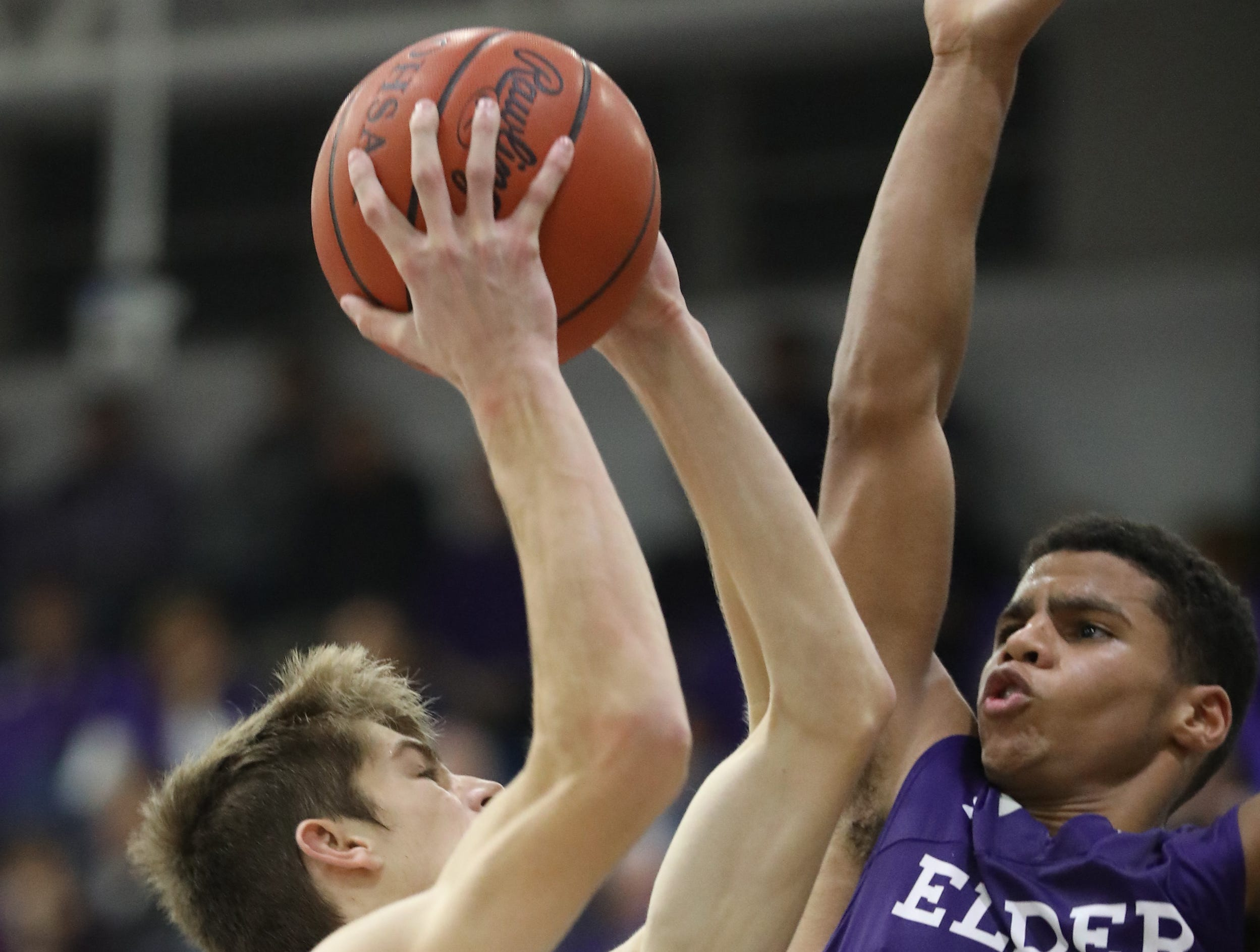 Elder guard Bryson Merz (23) tries to block a shot by St. Xavier forward Hank Thomas (20) during their basketball game Friday, Feb. 1, 2019.