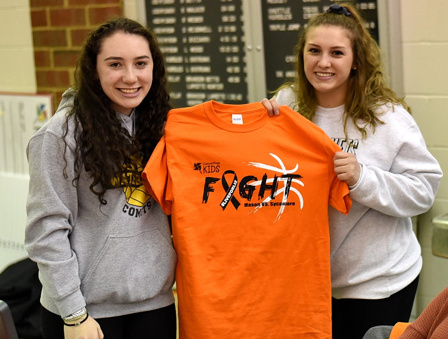 Shosi Ploetz and Katherine Draginoff of Mason show of this year's T-shirt in the Third Annual Live for Liz Fight For Cancer Free Kids Basketball Game, Feb. 1, 2019.