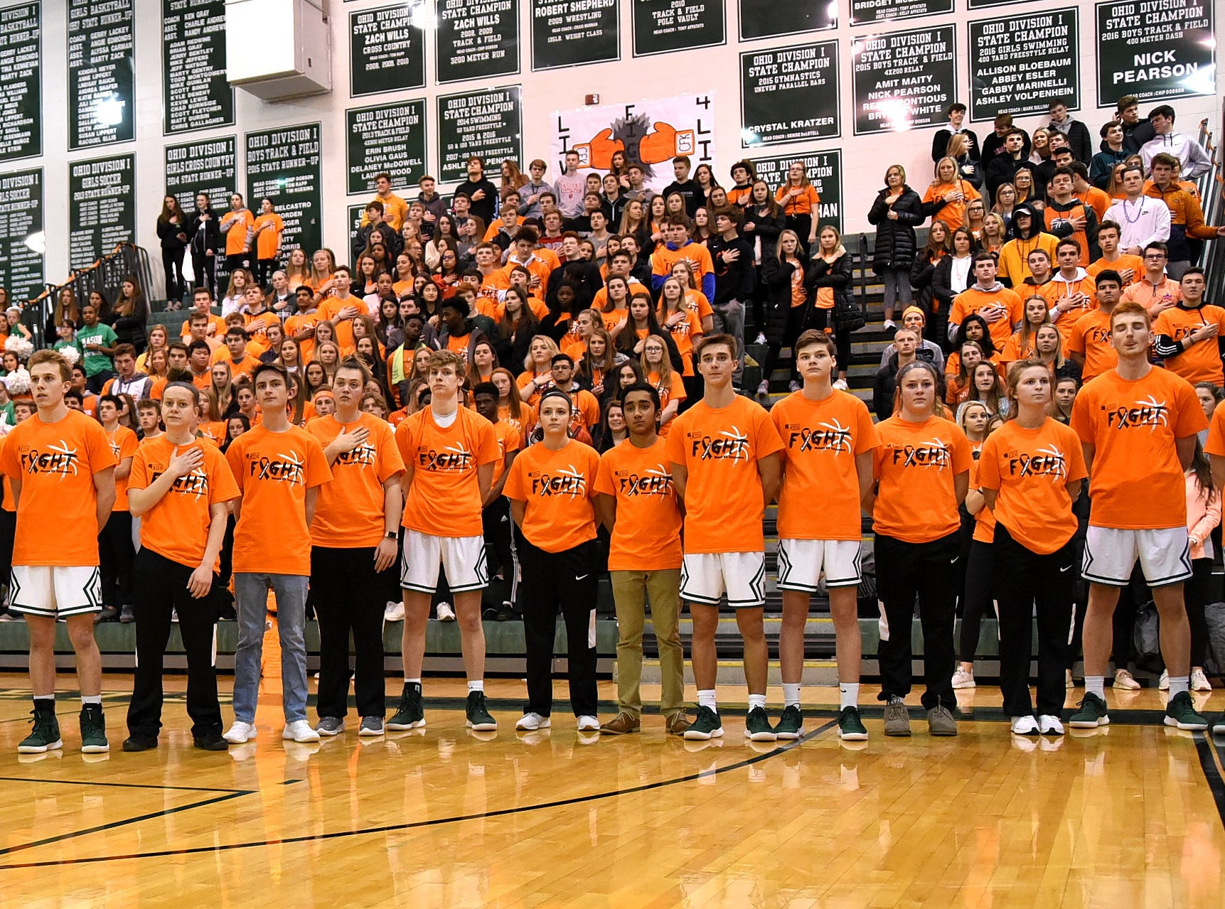 Gents and Lady Comets are flanked by the Mason student body during the National Anthem at the Third Annual Live for Liz Fight For Cancer Free Kids Basketball Game, Feb. 1, 2019.