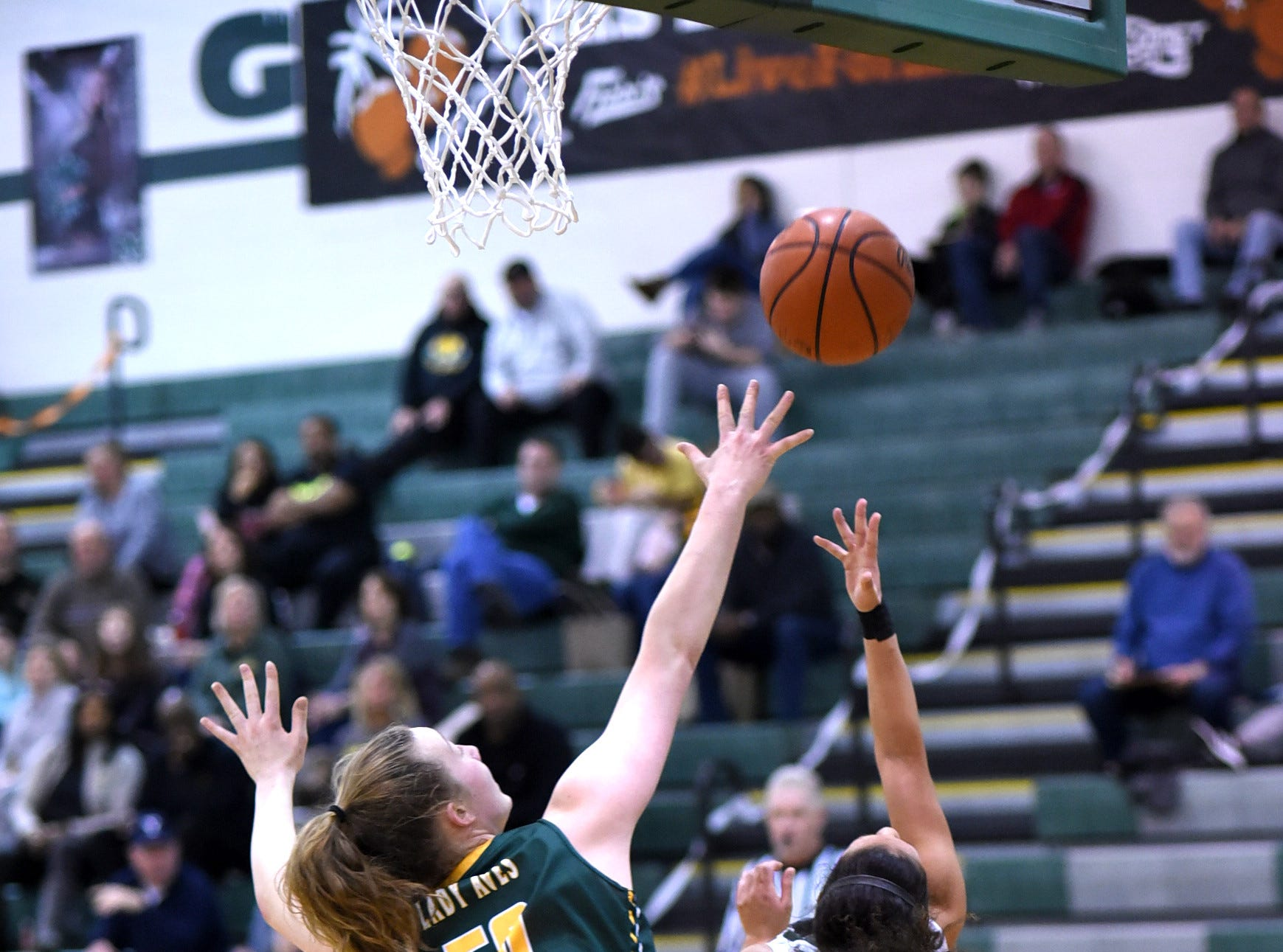 Mason's Sade Tucker (3) drops in a backward, over-the-head layup for the Comets as Sycamore's Brianna Counts (50) defends in the Third Annual Live for Liz Fight For Cancer Free Kids Basketball Game, Feb. 1, 2019. Mason girls won 47-29.