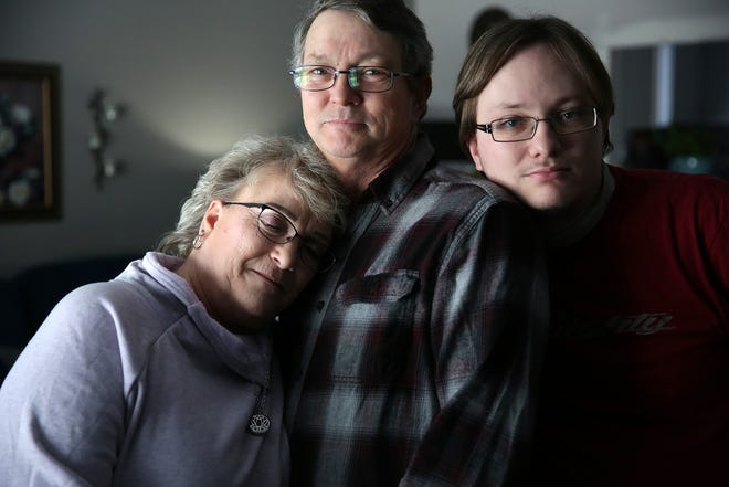 Don Jolliff, 58, of Harrison Twp, center embraces his wife, Debbi, 56, and son Justin Jolliff, 26, at their home on Saturday, Feb. 2, 2019.